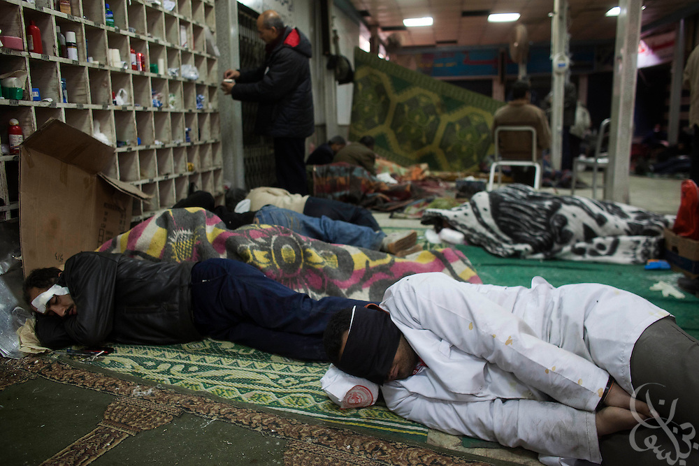 Wounded Egyptian protesters and doctors alike try to catch some sleep inside  a small field hospital inside a mosque just off Tahrir square following a long night of clashes February 03, 2011 in Cairo, Egypt. Protesters both pro and anti-Hosni  Mubarak clashed for the second day in a row, with hundreds wounded on each side. (Photo by Scott Nelson)