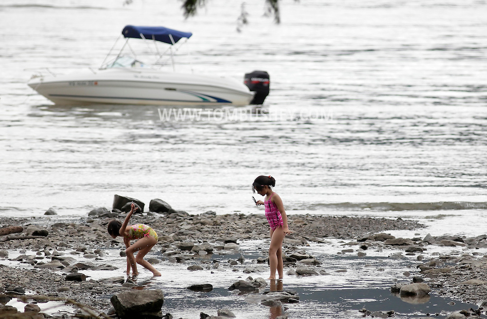 Cornwall-on-Hudson, New York - Two girls walk through the water on the shore of the Hudson River during RiverFest at Donahue Park on June 4, 2011.