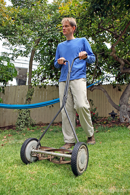 A man mows the grass with an environmentally-friendly push reel mower.