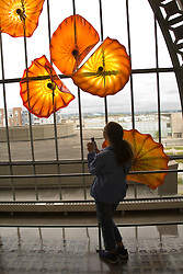 Teenage girl gazing at Monarch Window of glass art by Dale Chihuly, Union Station, Tacoma, Washington, USA