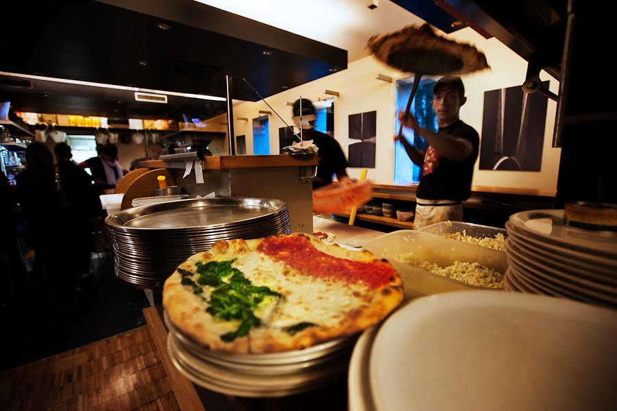 Piccola Piedigrotta is a very popular pizzeria in the centre of Reggio Emilia. A waiter serves a Tricolore pizza.