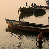 The activity of the ghats of Varanasi, people performing ablutions and the rowboats getting ready.