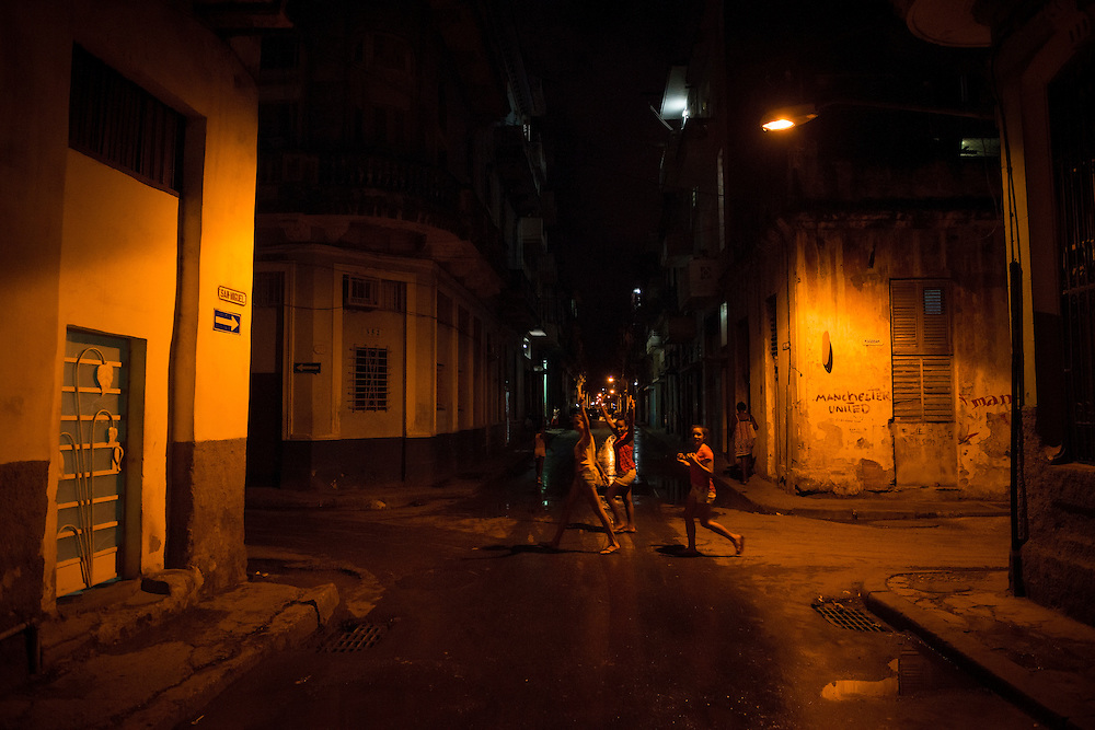 """Three girls walking down Escobar Street in Centro Habana raise their hands and smile after spotting a photographer shooting scenes at the intersection. Someone has painted """"Manchester United"""" on a wall. Havana, Cuba"""