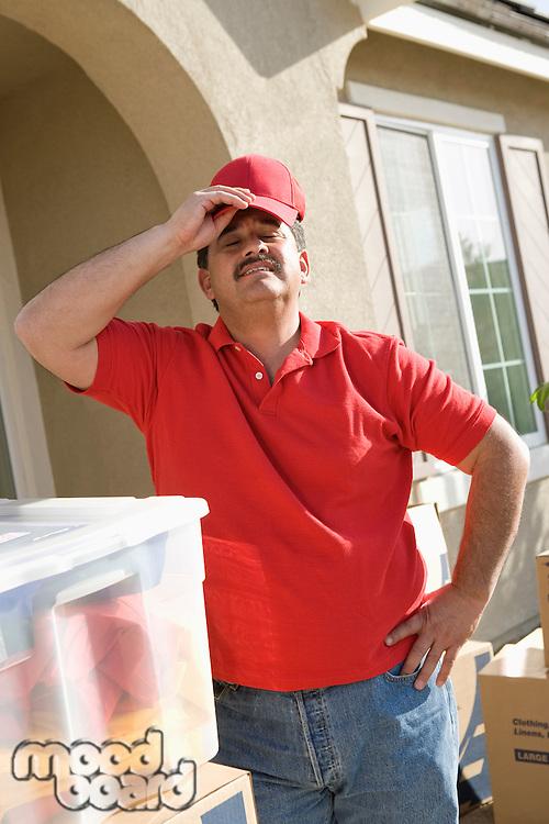 Mid-adult man putting on baseball cap, outdoors