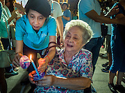 12 AUGUST 2015 - BANGKOK, THAILAND: Thais light candles at a shopping mall in Bangkok to honor Queen Sirikit of Thailand on her 83rd birthday. Queen Sirikit was born Mom Rajawongse Sirikit Kitiyakara on August 12, 1932. She is the queen consort of Bhumibol Adulyadej, King (Rama IX) of Thailand. She met Bhumibol in Paris, where her father was the Thai ambassador. They married in 1950, she was appointed Queen Regent in 1956. The King and Queen had one son and three daughters. She has not made any public appearances since her hospitalization in 2012. Her birthday is celebrated as Mother's Day in Thailand, schools and temples across Thailand hold ceremonies to honor the Queen and mothers.     PHOTO BY JACK KURTZ