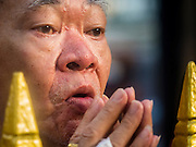 "04 SEPTEMBER 2015 - BANGKOK, THAILAND: A man who couldn't get into the shrine Friday morning prays in front of Erawan Shrine during a special rededication ceremony. A ""Holy Religious Ceremony for Wellness and Prosperity of our Nation and Thai People"" was held Friday morning at Erawan Shrine. The ceremony was to regain confidence of the Thai people and foreign visitors, to preserve Thai religious customs and traditions and to promote peace and happiness inThailand. Repairs to Erawan Shrine were completed Thursday, Sept 3 after the shrine was bombed on August 17. Twenty people were killed in the bombing and more than 100 injured. The statue of the Four Faced Brahma in the shrine was damaged by shrapnel and a building at the shrine was damaged by debris.     PHOTO BY JACK KURTZ"