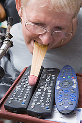 Woman with Cerebral Palsy using her mouth to operate a TV remote control,