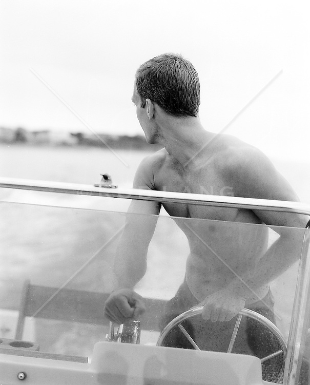 Man looking back while steering a motor boat