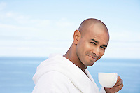Man in bathrobe with cup of tea in front of ocean head and shoulders