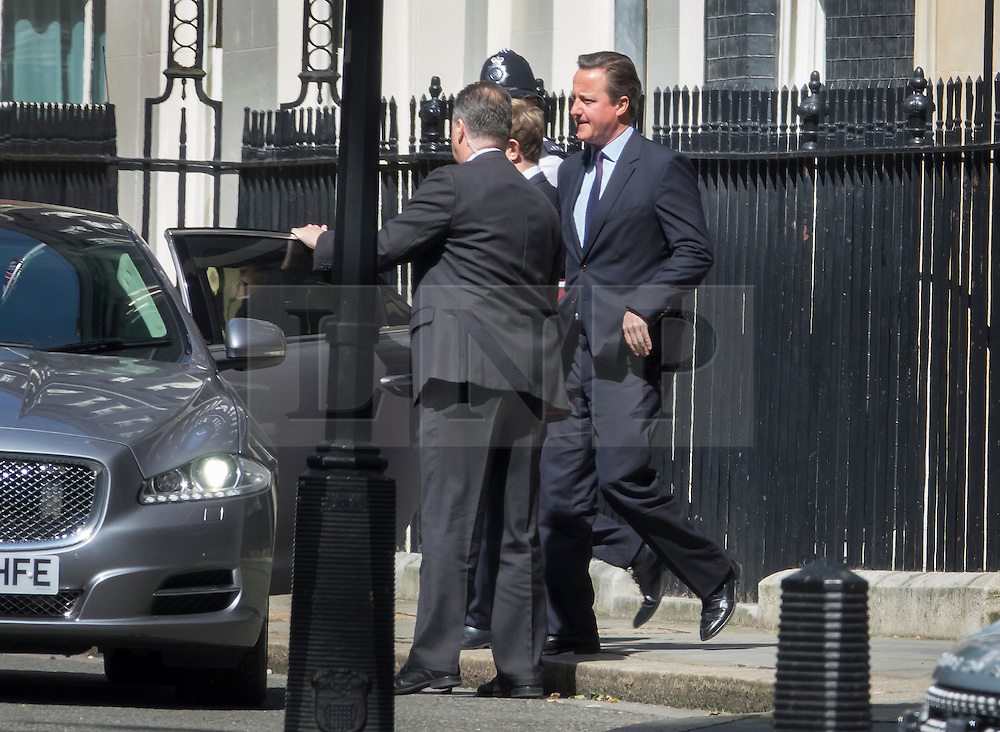© Licensed to London News Pictures. 06/07/2016. London, UK. Prime Minister David Cameron appears to fly across Downing Street as he leaves Number 10 for Parliament. Mr Cameron's left foot has accidentally lined up with the foot of one of his bodyguards to create the illusion that he is levitating. Photo credit: Peter Macdiarmid/LNP