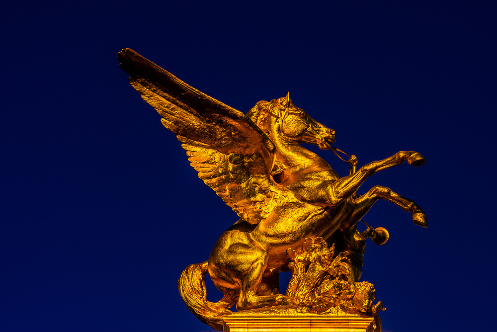 Gilded sculptures with winged horses sit at the ends of the Pont Alexandre III (bridge) across the Seine River. The bridge is the most ornate in the city. Paris, France.