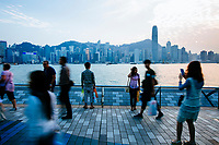 People walk along the boardwalk at dusk in Kowloon with a view toward Hong Kong behind them.