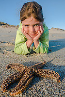 A child watches a starfish along the coastline of the De Hoop Marine Protected Area, Western Cape, South Africa