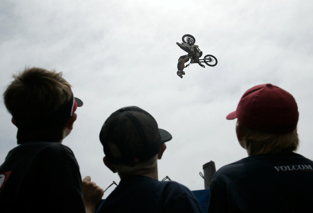Wesley Theobald, 11, Zane Weber, 10, and Wyatt Theobald, 9, watch the Freestyle Motor Cross Demo at the U.S. Open of Surfing in Huntington Beach Friday July 30, 2004.