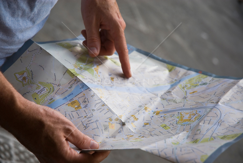 detail of a man pointing to a location on a map.
