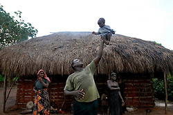 Msese holds a child up outside a house where lions were roaming the night before near Navunga. Ami Vitale