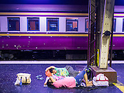 20 MARCH 2015 - BANGKOK, THAILAND: People sleep in front of a third class train at Hua Lamphong train station in Bangkok. The State Railways of Thailand (SRT), established in 1890, operates 4,043 kilometers of meter gauge track that reaches most parts of Thailand. Much of the track and many of the trains are poorly maintained and trains frequently run late. Accidents and mishaps are also commonplace. Successive governments, including the current military government, have promised to upgrade rail services. The military government has signed contracts with China to upgrade rail lines and bring high speed rail to Thailand. Japan has also expressed an interest in working on the Thai train system. Third class train travel is very inexpensive. Many lines are free for Thai citizens and even lines that aren't free are only a few Baht. Many third class tickets are under the equivalent of a dollar. Third class cars are not air-conditioned.   PHOTO BY JACK KURTZ