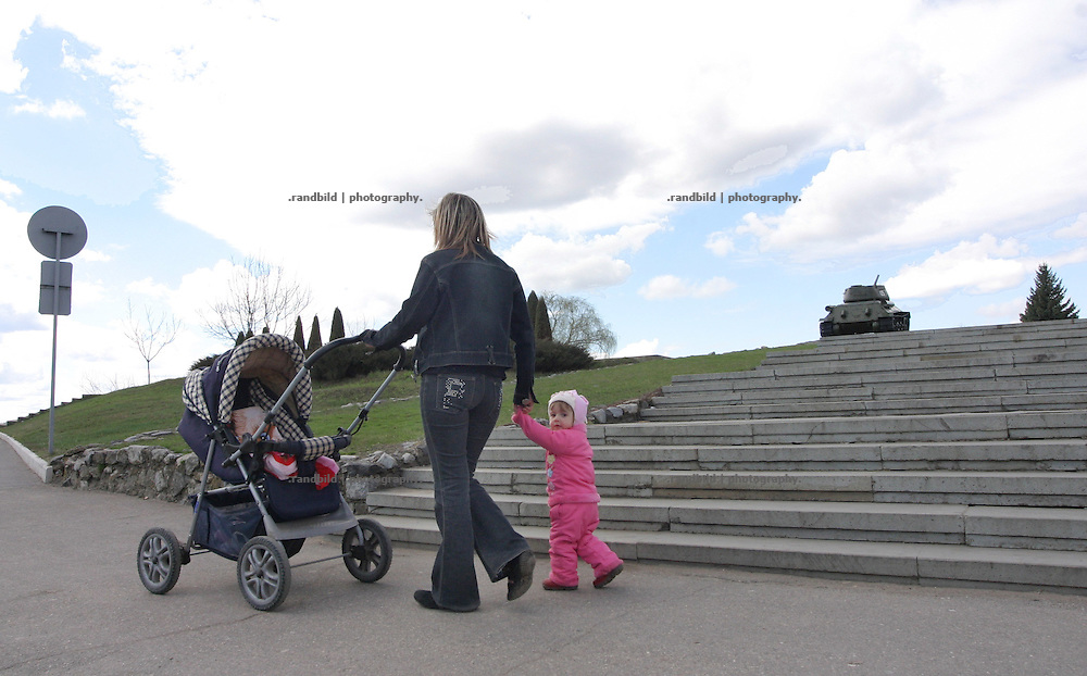 Eine junge Mutter geht mit ihrem Kind an einem Panzer vorbei, der als Kriegsdenkmal in Tiraspol/Transnistrien steht. / A young mother with her child walks by a tank which is a war memorial in Tiraspol/Transnistria.
