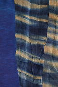 Collection of fabrics dyed using indigo in both block colour and stripes, by fabric artist Betty de Paris, in her studio at Cite Aubry, in the 20th arrondissement of Paris, France. The Japanese indigo vat is a traditional dyeing technique using indigo leaf compost, a vegetal process involving no chemicals. Betty de Paris learned her art of traditional stencil dyeing and finishing from a master in Kyoto, Japan. Working as an artist, designer, consultant and Japanese interpreter, she has participated in numerous museum projects and workshops, regularly exhibits her work and speaks at international conferences. Picture by Manuel Cohen