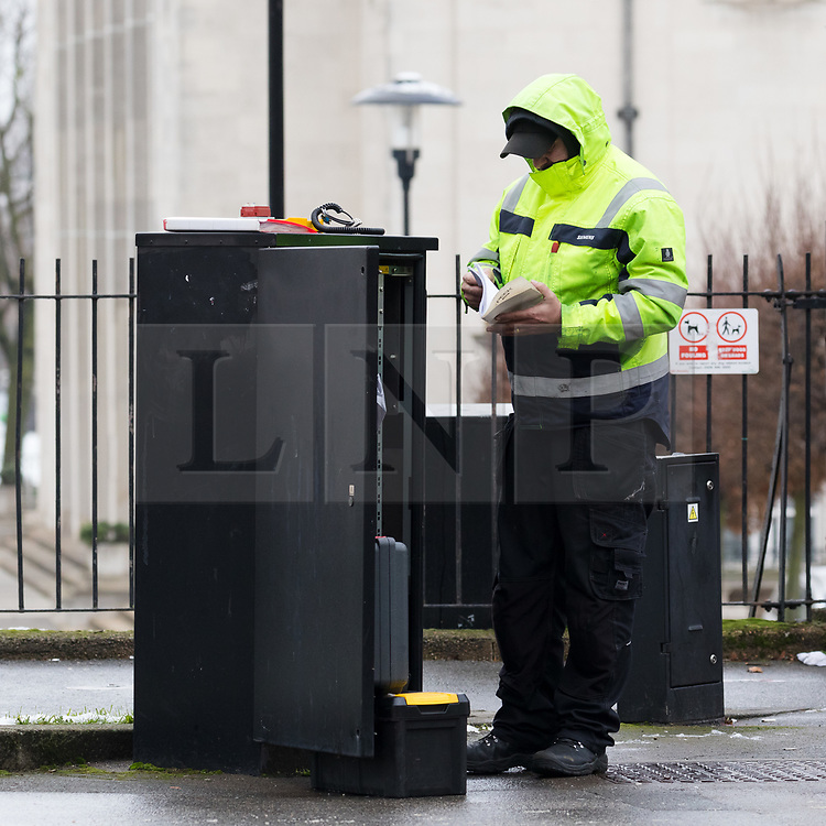 © Licensed to London News Pictures. 23/01/2019. London, UK.  An investigator at the electricity box next to the pedestrian crossing in Forest Road, Walthamstow opposite the Town Hall where a 21 year old woman following a collision with a police car responding to a 999 call last night.  Photo credit: Vickie Flores/LNP