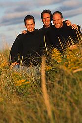 Three men in sweaters in tall beach grass