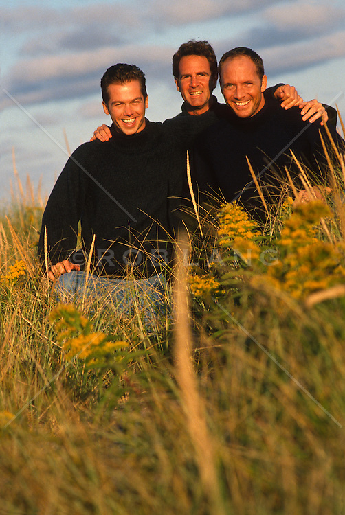Three men in sweaters in tall beach grass