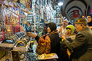 Shopper views jewelry on display for sale in the Misir Carsisi Egyptian Bazaar food and spice market in Istanbul, Turkey
