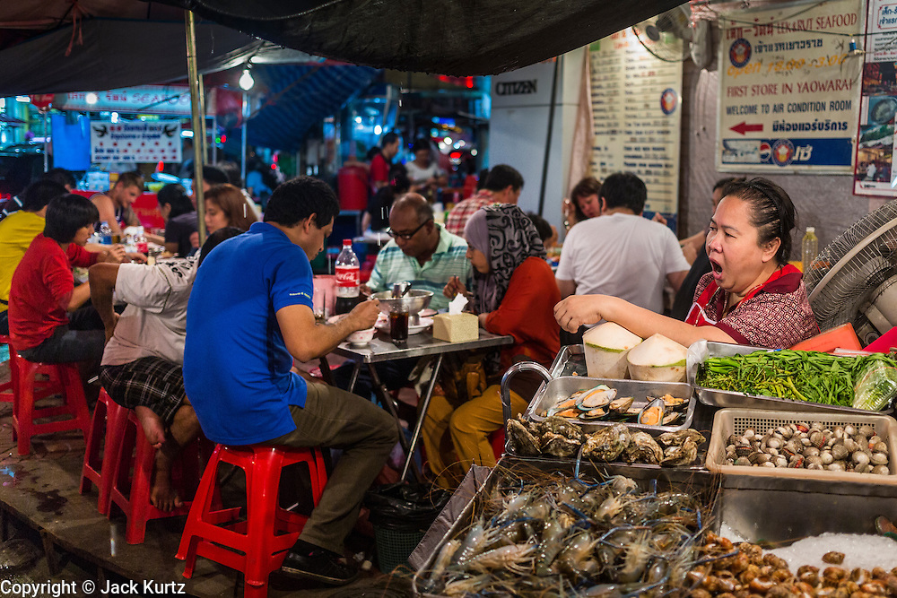18 SEPTEMBER 2013 - BANGKOK, THAILAND:  A worker yawns  while customers eat at Lek and Rut Seafood stand in the Chinatown section of Bangkok. Lek and Rut Seafood was one of the first street stall restaurants in Bangkok and is more of a pop up restaurant than a street food stall. It has sit down service and full menus, but seating is on the street and sidewalk and food is prepared in portable cookers that are brought out to the street when the restaurant opens. Thailand in general, and Bangkok in particular, has a vibrant tradition of street food and eating on the run. In recent years, Bangkok's street food has become something of an international landmark and is being written about in glossy travel magazines and in the pages of the New York Times.     PHOTO BY JACK KURTZ