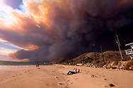 People enjoy the day in the beach as the heavy smoke rises over the the Santa Monica Mountains during the Woolsey fire in Malibu, Calif., Friday, Nov. 9, 2018. The Woolsey Fire was a destructive wildfire that burned in Los Angeles and Ventura Counties of the U.S. state of California. The fire ignited on November 8, 2018 and burned 96,949 acres of land.