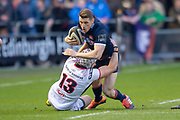 Mark Bennett (#13) of Edinburgh Rugby is tackled by Luke Marshall (#13) of Ulster Rugby during the Guinness Pro 14 2018_19 match between Edinburgh Rugby and Ulster Rugby at the BT Murrayfield Stadium, Edinburgh, Scotland on 12 April 2019.