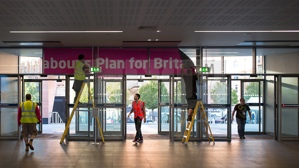 """© Licensed to London News Pictures . 24/09/2014 . Manchester , UK . Workers tearing down """" LABOUR'S PLAN FOR BRITAIN'S FUTURE """" sign at the end of the Labour Party Conference in Manchester . Photo credit : Joel Goodman/LNP"""