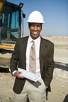 Surveyor holding blueprints on construction site, portrait