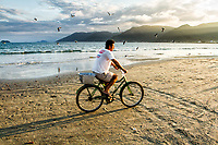Homem andando de bicicleta na Praia do Pântano do Sul. Florianópolis, Santa Catarina, Brasil. / Man riding a bicycle at Pantano do Sul Beach. Florianopolis, Santa Catarina, Brazil.