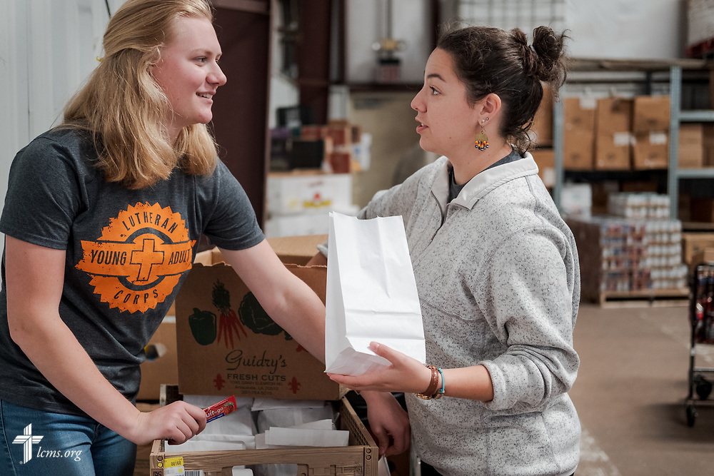 Young Adult Corps participants Courtney Haag and Madison Ezzell serve together at a food distribution warehouse on Wednesday, April 4, 2018, in New Orleans. LCMS Communications/Erik M. Lunsford
