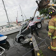 Members of the Babylon Fire Department work to remove an SUV from the canal near 112 Shore Road in Babylon Friday, June 19, 2015.