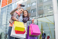 Female friends with shopping bags taking self portrait through mobile phone against store
