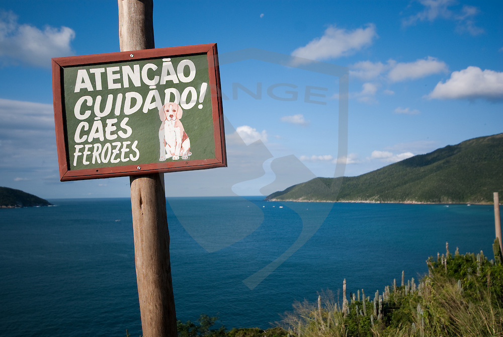 warning!  ferocious dog!  a sign protects private property with the atlantic ocean and mountain landscape near prainha beach in rio de janeiro brazil.