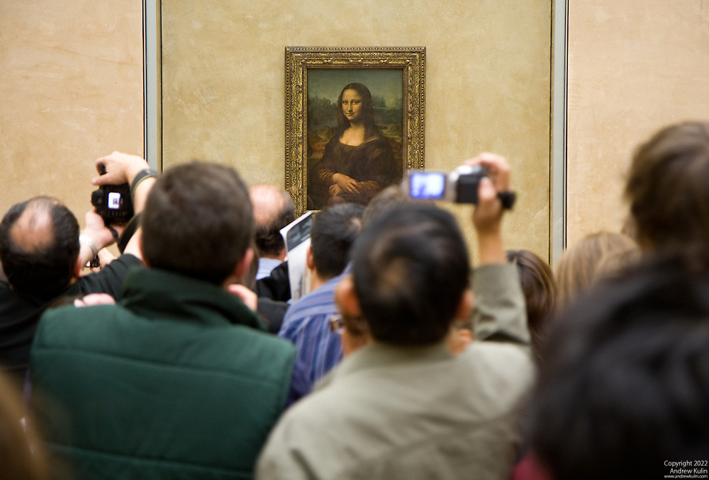 The Mona Lisa and the mass of people crowding around her for a photograph.