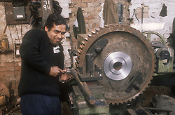Metal work shop in the Punjab; India; with worker operating machinery,