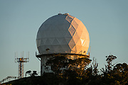 This remote yet prominent state radar station with radome shaped like golf ball surveils the Hawaii region, just above Kalalau Lookout at 4000 feet elevation on the island of Kauai, USA. The Kokee AFS Air National Guard Radar Site, is a state militia unit under jurisdiction of the Governor of Hawaii through the office of the Hawaii Adjutant General, unless federalized by order of the President of the United States, as it is an Air Reserve Component (ARC) of the United States Air Force (USAF). This remote Air Force Station (AFS) on Kauai has its headquarters at Joint Base Pearl Harbor-Hickam in Honolulu. The scenic Koke'e State Park is in northwestern Kauai in the Hawaiian Islands, USA. Perched on a plateau between 3200 and 4200 feet, the park gets temperatures at least 15 degrees Fahrenheit cooler than at sea level. Koke'e receives 50-100 inches of rain per year, mostly from October to May. Its forests are dominated by Acacia koa and ohia lehua (Metrosideros polymorpha) trees.