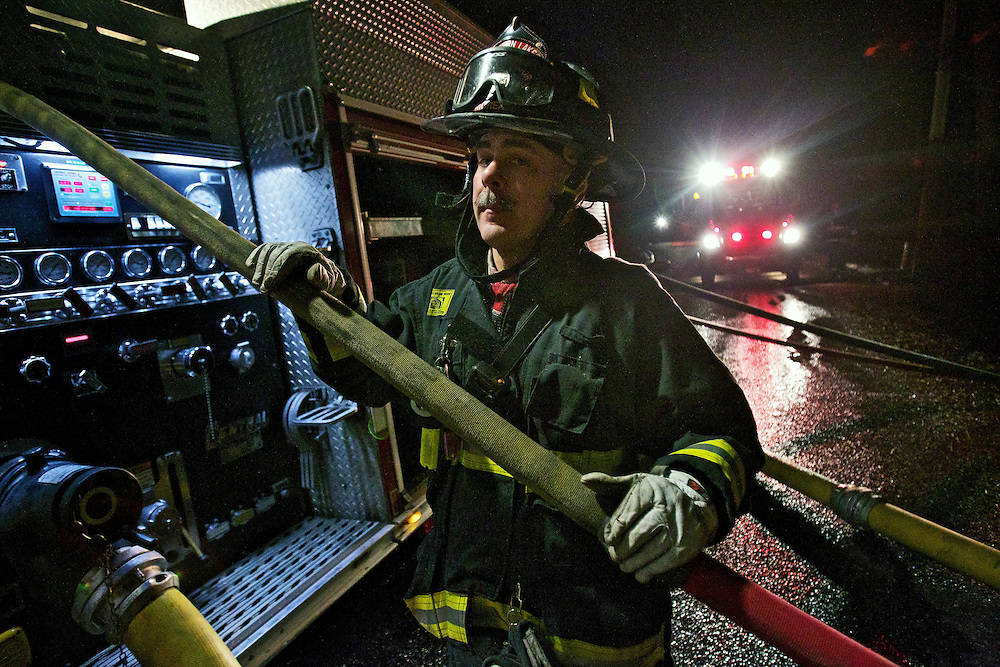 Jerry Moreau, a firefighter with Northern Lakes Fire Protection District, stands by near the pump controls for a fire engine Tuesday as crews extinguish a structure fire on Deep Water Drive in Hayden.