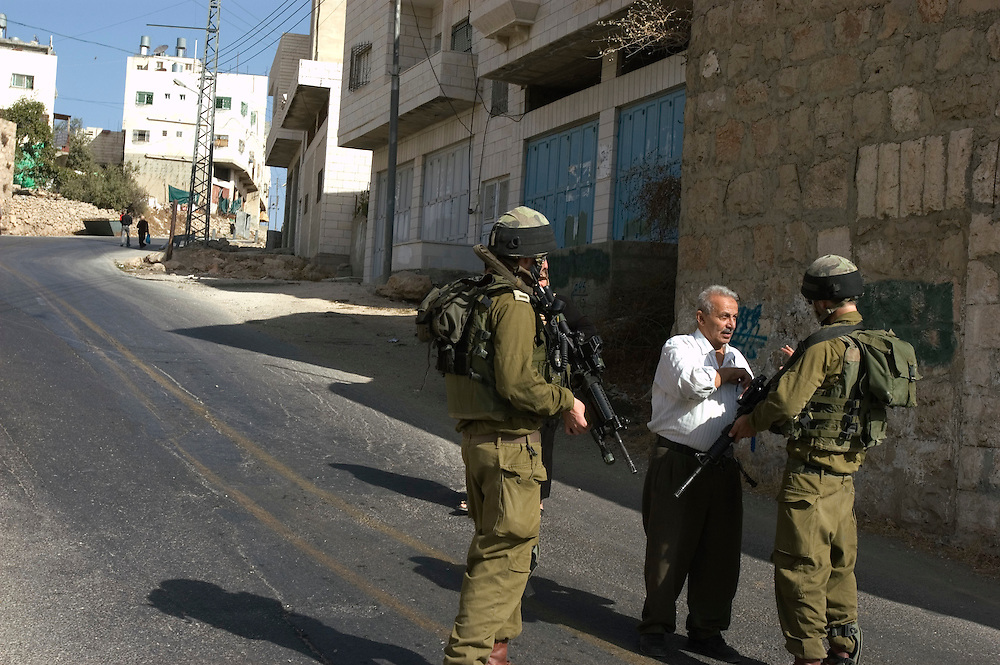 Israeli soldiers check the identity papers of a Palestinian man in the streests of Hebron. Some six hundred Jews live in the heart of Hebron's old city surrounded by over 160,000 Palestinian inhabitants..Hebron, Israel. 02/11/2007.Photo © J.B. Russell/Blue Press