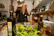 Astrid Holmann of the Hollmann Sturm family in Hamburg, Germany preparing salad dressing for supper in her kitchen. They were photographed for the Hungry Planet: What I Eat project with a week's worth of food in June. Model Released.
