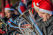 A bras band entertains from teh bandstand - Thosuands of runners, of all ages, in santa suits and other Christmas costumes runaround Clapham Common for Great Ormond Street Hospital and for fun. London 30 Nov 2016