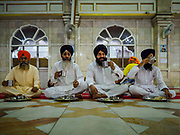 "25 FEBRUARY 2019 - BANGKOK, THAILAND:  Sikh men eat during the morning ""Langar"" (communal meal) at the Gurdwara Siri Guru Singh Sabha. The Gurdwara serves about 500 free meals Monday through Saturday and about 1,000 free meals on Sundays. Although Sikhs are not vegetarians, the Langar meals are vegetarian so anyone can them without violating a religious edict on diet. The meals are free for anyone who walks into the Gurdwara, regardless of their religion or nationality. The Gurdwara Siri Guru Singh Sabha in Bangkok is one of the largest Sikh Gurdwaras (temples) outside of India. It is in Bangkok's ""Little India"" neighborhood, next to Chinatown. Construction on the Gurdwara started in 1979 and finished in 1981.         PHOTO BY JACK KURTZ"