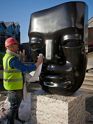 © licensed to London News Pictures. London, UK 15/01/12. Master stone-carver Paul Vanstone cleans his gaint scuplture after positioning it outside Business Design Centre in London for the 24th London Art Fair, the UK's largest fair for Modern British and contemporary art. Photo credit: Tolga Akmen/LNP