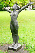 Stone statue of a naked young woman with outstretched arms at the National Opera Gardens, Riga, Latvia