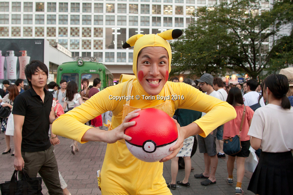 """July 24, 2016, Tokyo, Japan: This is Kohachu, a Japanese man who loves Pokemon so much he created his own character that he regularly wears in costume at Hachiko Plaza in front of Tokyo's Shibuya Station, a major commuter hub and youth culture center of the city. Kohachu is happy to pose for photos and hands his out business cards detailing his Pokemon stats. This includes his type """"Denki Hito"""" or Electric Human, his category """"Zentaitsu Pokemon"""" or full body suit Pokemon, height and weight. Kohachu frequents Shibuya station on a regular basis and has a strong social media presence. On 7/22/16, Pokemon Go was released in Japan which took the country by storm and is causing concerns safety concerns by the Japanese government and police. (Torin Boyd/Polaris)."""