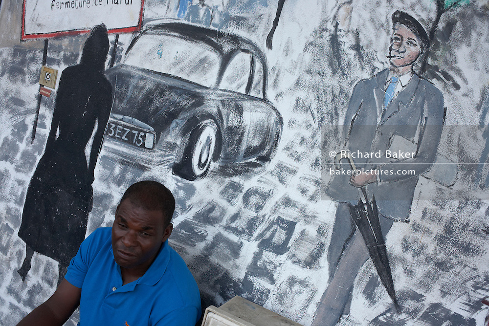 A man of Creole descent relaxes late-afternoon in front of a mural showing a scene of Parisian life, in colonial Kourou.