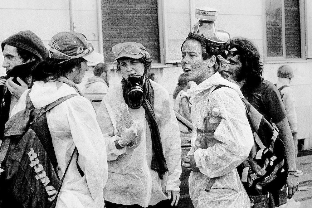 Genova, venerdì 20 luglio 2001. Giornata delle piazze tematiche. Corteo della disobbedienza civile. Nei pressi di via Invrea, durante gli scontri un gruppo di volontari del supporto medico osserva con spavento quanto sta avvenendo nei paraggi.